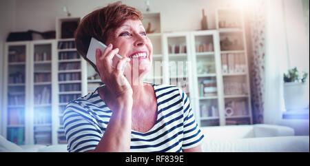 Senior Woman talking on mobile phone in living room