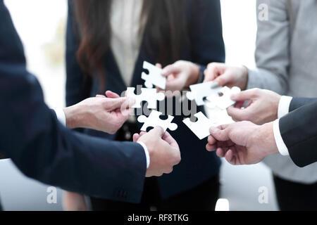 Groupe de gens d'affaires d'assembler un puzzle, l'appui de l'équipe Banque D'Images