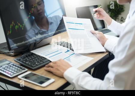 L'équipe d'affaires Bourse Finance trading analyse graphique sur plusieurs écrans d'ordinateur dans le bureau commercial moderne, de financement et d'investissement concept. Banque D'Images