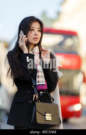 70e76508c49 Femme dans un imperméable rouge steampunk  Photo de jeune brunette avec  téléphone sur fond de ville en bus pour marcher au printemps