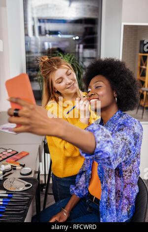 L'Afrique de l'étonnant modèle américain avec le rouge à lèvres corail selfies rendant Banque D'Images