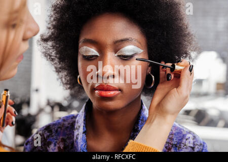 Jeune blonde avec styliste ongles noir faire le maquillage pour un modèle Banque D'Images