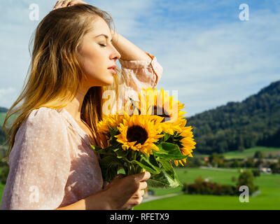 Photo d'un happy young woman holding sunflowers in the sunshine. Banque D'Images