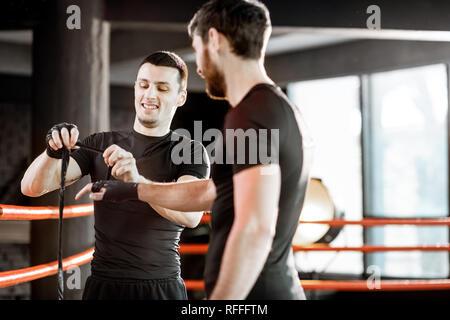 Boxe bandage d'enroulement sur le poignet d'un homme, la préparation de la boxe sur le ring de boxe à la salle de sport Banque D'Images