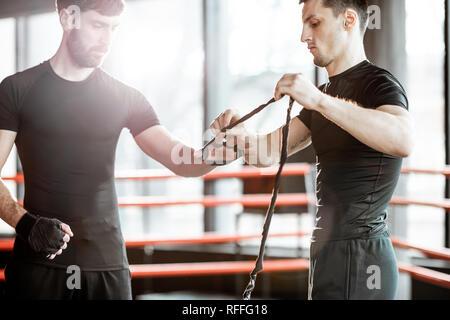 Bobinage formateur bandage sur le poignet d'un homme, la préparation de la boxe sur le ring de boxe à la salle de sport Banque D'Images