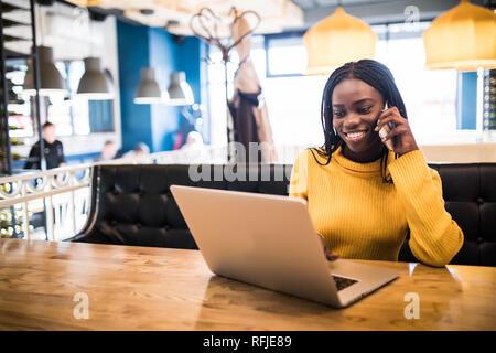 Closeup portrait of young African woman relaxing in cafe avec ordinateur portable et faire appel Banque D'Images