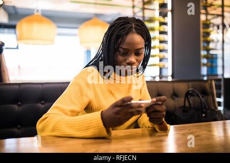 Jeune femme africaine au café à boire du café et à l'aide de mobile phone Banque D'Images