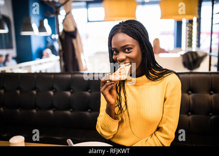 Young african american woman eating pizza in cafe
