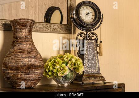 Le décor intérieur arrangement avec miroir, réveil, vase et floral. Banque D'Images