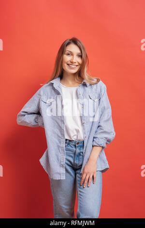 Joli poil long modèle féminin posant avec un visage souriant d'expression sur fond rouge. Close-up portrait of a casual fille européenne avec des lunettes standi Banque D'Images
