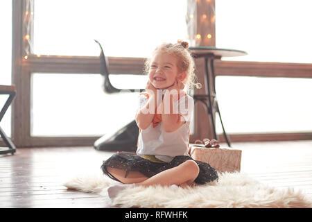 Heureuse petite fille assise sur le tapis dans le salon.