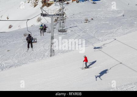 Double-président téléski avec les gens sur les pistes de ski sur une journée d'hiver ensoleillée