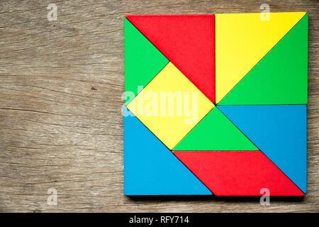 Puzzle jouets colorés en forme carré géométrique sur fond de bois Banque D'Images
