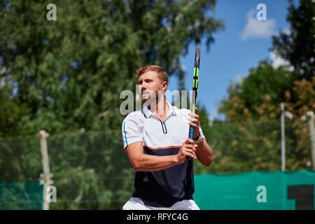 Jeune homme de sportwear joue au tennis sur la cour. Banque D'Images