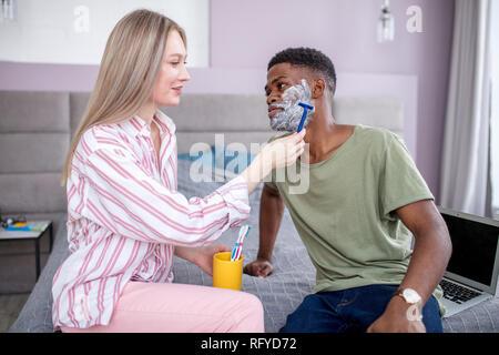 L'homme africain de son visage en face de l'mirrow, dans salle de bains monochrome gris Banque D'Images
