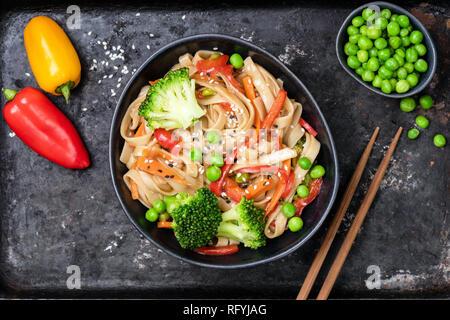 Sauté de légumes avec les nouilles Udon, brocoli, carottes, poivrons et petits pois dans un bol sur fond noir. Vue d'en haut Banque D'Images