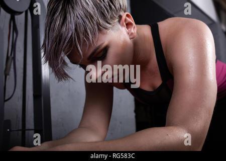 Dans les vêtements de sport féminins debout dans la salle de sport et à la  recherche 521a886ff62