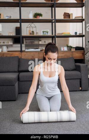 Jeune femme tapis de sol fitness matériel roulant pour la pratique du yoga à la maison Banque D'Images