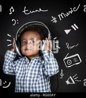 Portrait d'un mignon petit garçon afro-américains avec plaisir à l'écoute de la musique, happy child wearing headphones isolated sur fond noir avec différents Banque D'Images