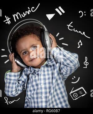 Adorable petit garçon afro-américains avec plaisir à l'écoute de la musique, happy child wearing headphones, portrait sur fond noir avec différentes encore de Banque D'Images