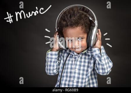 Cute little african american boy wearing earphones, l'écoute et l'enregistrement des chansons de bébé, portrait sur fond noir, happy little singer Banque D'Images