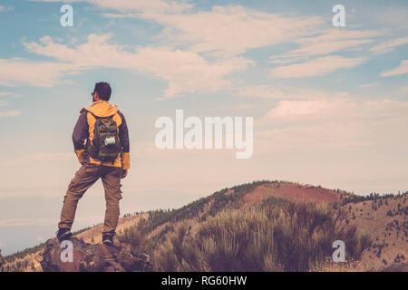 Homme randonnée au coucher du soleil les montagnes avec sac à dos léger Vie Voyage wanderlust adventure concept vacances piscine seul dans la nature - bleu Banque D'Images