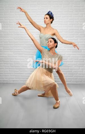 Vue avant du ballet dancers performing professionnel extra en studio. Les jeunes ballerines en beige et bleu robes garder les mains en l'air et à la ci-dessus. Concept de la danse de ballet et d'élégance. Banque D'Images