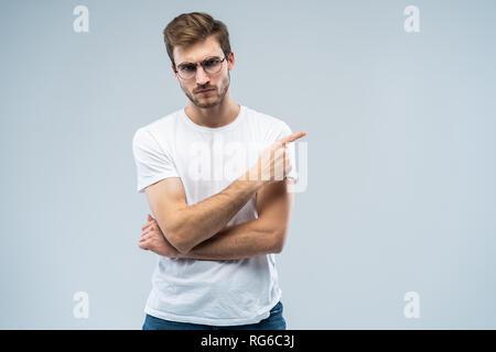 Portrait d'un jeune homme en colère pointant les doigts à copier sur son espace isolé sur fond gris palm. Banque D'Images