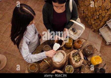 High angle view of shop assistant l'écopage de farine pour le client dans une boutique d'emballage. Zéro déchets shopping.