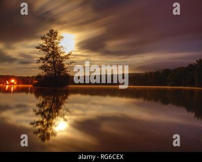 Et l'île du lac mystérieux dans fullmoon nuit. Matin brouillard sur un lac. Petite île avec des arbres moon light Banque D'Images