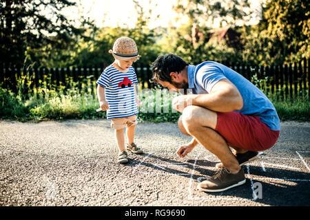 Père de marelle dessin sur l'asphalte alors que son petit-fils le regarder Banque D'Images