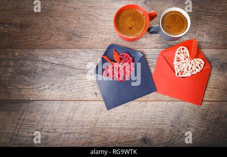 Composition festive sur table en bois rustique, rouge et gris mug avec du café, des coeurs dans des enveloppes, les fleurs de rose. Copier l'espace. Anniversaire, fête des mères, Valen Banque D'Images