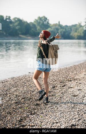 Jeune femme insouciante marchant au bord du fleuve