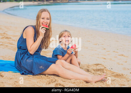 Famille heureuse mère et fils de manger une pastèque sur la plage. Les enfants mangent des aliments sains. Banque D'Images