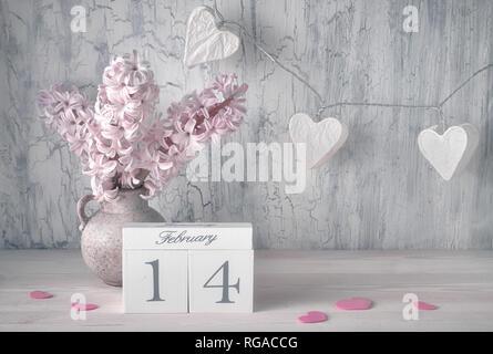 Valentines Day still life avec un calendrier, jacinthe rose fleurs et lumières garland en forme de cœur sur papier de fond rustique