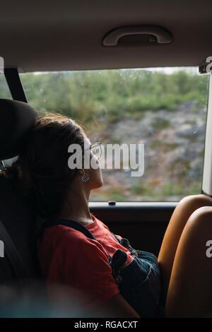 Jeune femme assise sur le siège arrière d'un van, à la fenêtre de sortie, voyageant par la Norvège