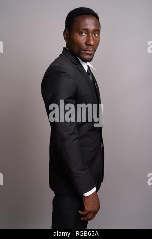 Beau jeune homme d'Afrique contre l'arrière-plan gris Banque D'Images
