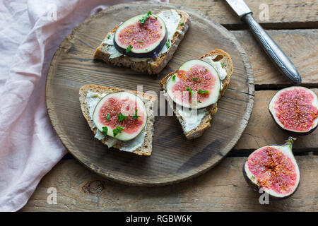 Tranches de pain beurrée de tranches de figues sur plaque de bois Banque D'Images