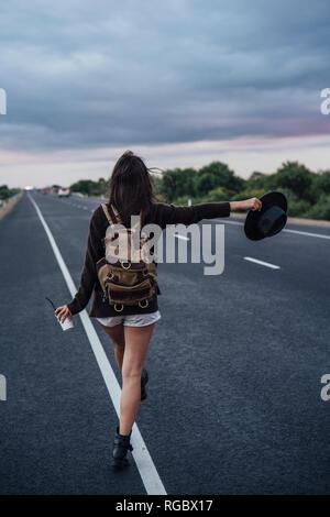 Vue arrière de l'auto-stop jeune femme avec sac à dos et boissons debout à la ligne latérale