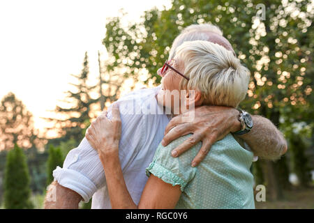 Happy senior couple hugging outdoors Banque D'Images