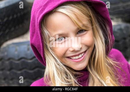 Portrait of smiling blonde girl wearing Hooded Jacket rose Banque D'Images