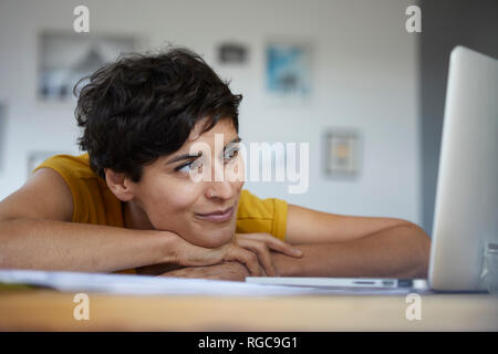 Smiling woman at home leaning on table looking at laptop Banque D'Images