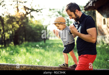 Père d'aider son petit-fils en équilibre sur une clôture Banque D'Images