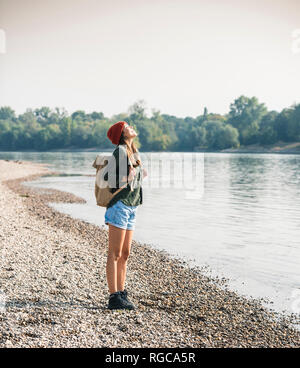Happy young woman standing at the riverside