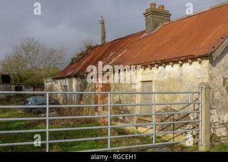 Entrée de ferme abandonnée cottage avec vieille voiture en basse-cour. Banque D'Images
