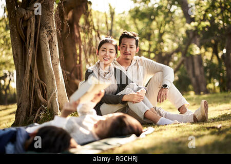 Deux enfants asiatiques little boy and girl having fun lying on grass lire un livre avec les parents assis à regarder en arrière-plan, l'accent sur les parents en b Banque D'Images