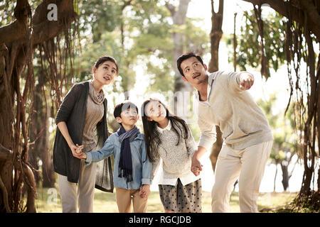 La famille asiatique avec deux enfants s'amusant à explorer les bois dans un parc. Banque D'Images