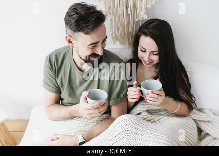 Heureux couple sitting in bed, boire du café, s'amuser