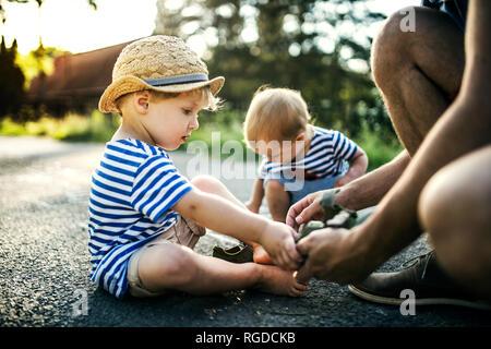 Père d'aider son petit-fils à la déshabiller ses chaussures Banque D'Images