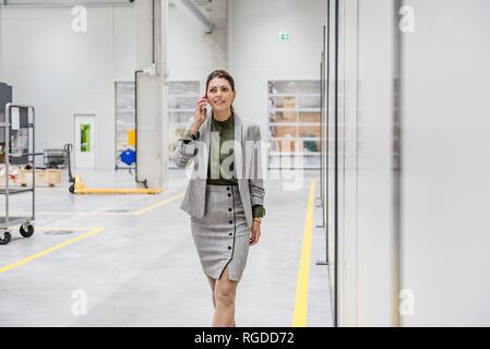 Businesswoman walking in atelier d'usine, parler au téléphone